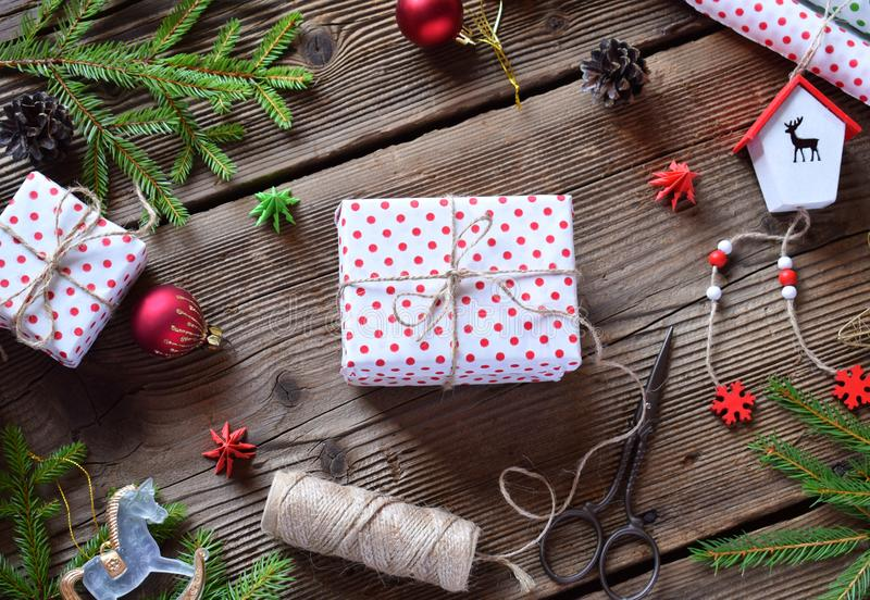 Gift wrapping. Christmas composition with present box, packing paper, festive decoration and fir tree branch. Preparation for holi royalty free stock photo