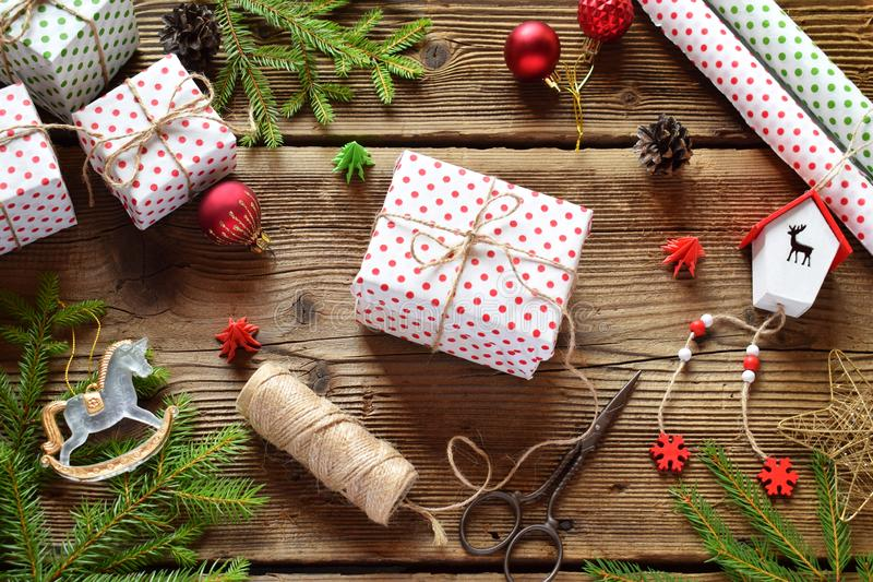 Gift wrapping. Christmas composition with present box, packing paper, festive decoration and fir tree branch. Preparation for holi stock photography