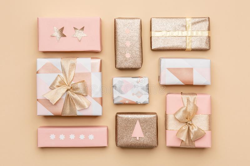 Gift wrapping composition. Beautiful nordic christmas gifts isolated on gold background. Pink and gold colored wrapped gift boxes. Gift wrapping composition royalty free stock photo