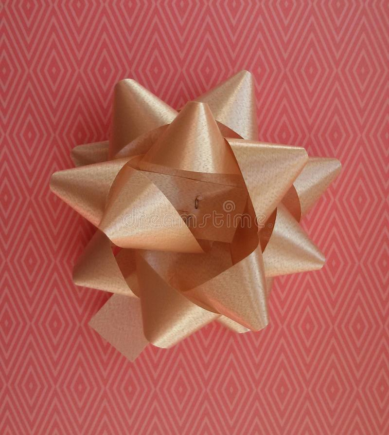 Gift wrapping idea. Pink paper and golden bow. Pink paper design and golden bow. Present wrapping idea royalty free stock images
