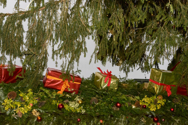 Gift wraps on stall roof at Xmas market time. Christmas tree, gift wraps and decorated spruce on stall roof at traditional Christmas market hold in city center royalty free stock images