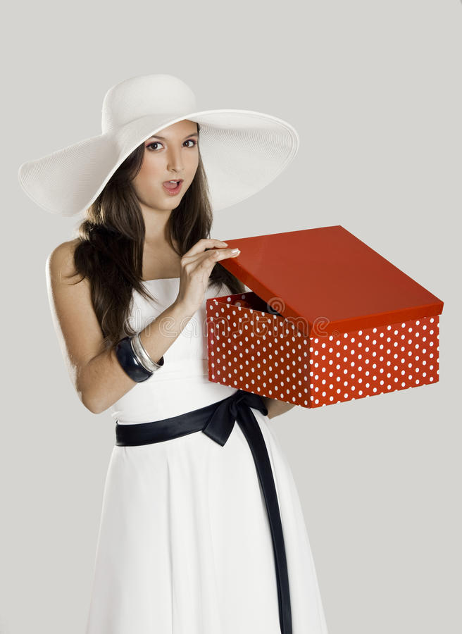 Gift for you. Beautiful and happy young woman holding a gift and pointing to you royalty free stock photo
