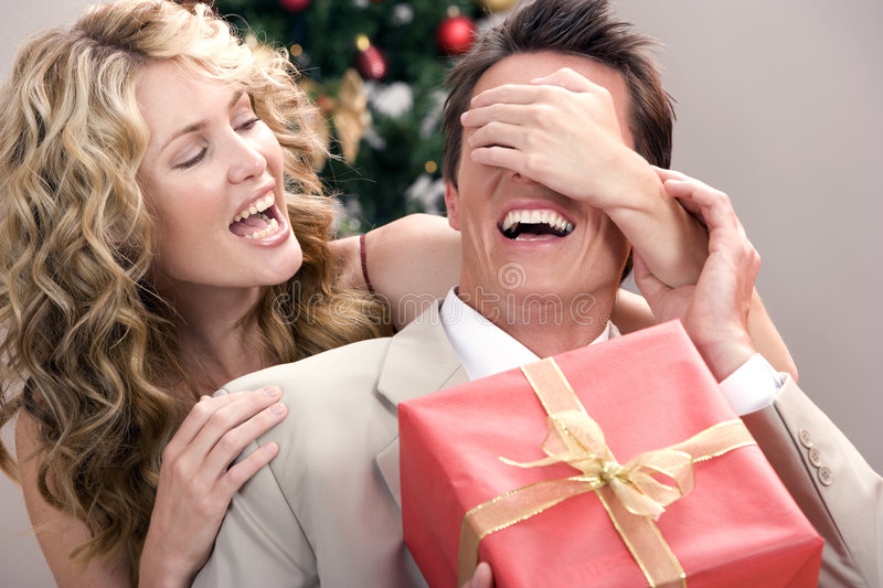 A gift for you!!. A beautiful wife giving her husband a christmas gift