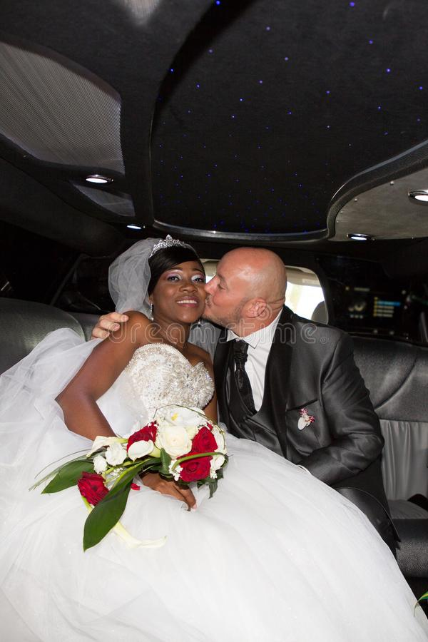 gifta bi-ras- amerikanska par i limousinebröllopbil arkivfoto