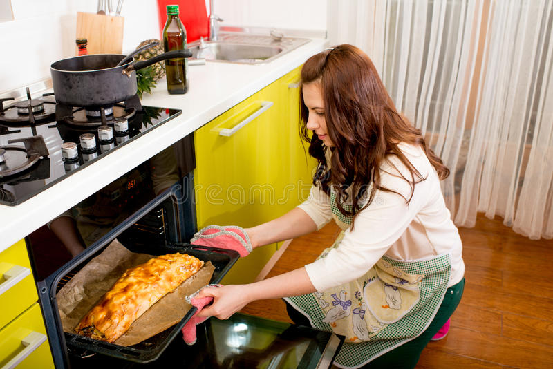 Gifta le par som sätter äpplet till ugnen på köket arkivfoto