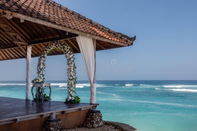 Gifta sig aktiveringen - brölloppergola, blommabåge och stolar för gäster nära havet, Bali, Indonesien arkivbild