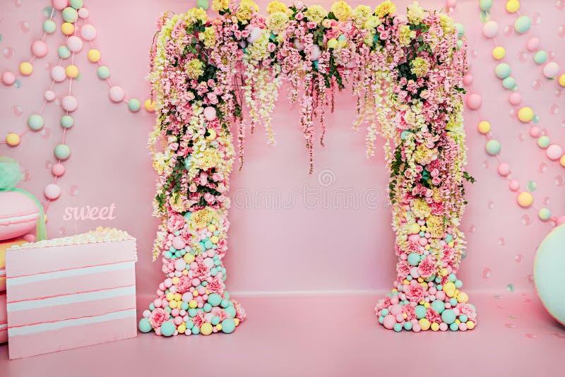 Gifta sig bågen inomhus Festliga garneringar med blommor och färgrika ballonger på rosa bakgrund arkivbild