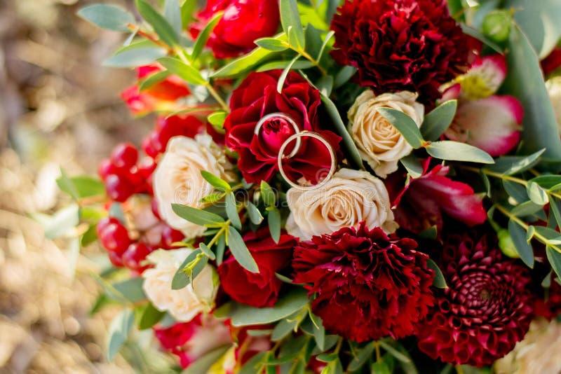 Gifta sig bakgrundsbuketten och cirklar Brudens bukett av röda och rosa blommor och grönska, med färgmarsala förklaringnolla royaltyfria foton