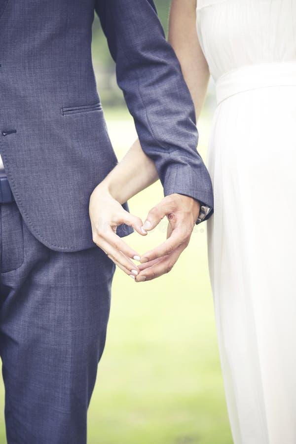 Gifta sig - brud- och fiancevisninghjärta formar med händer arkivfoton