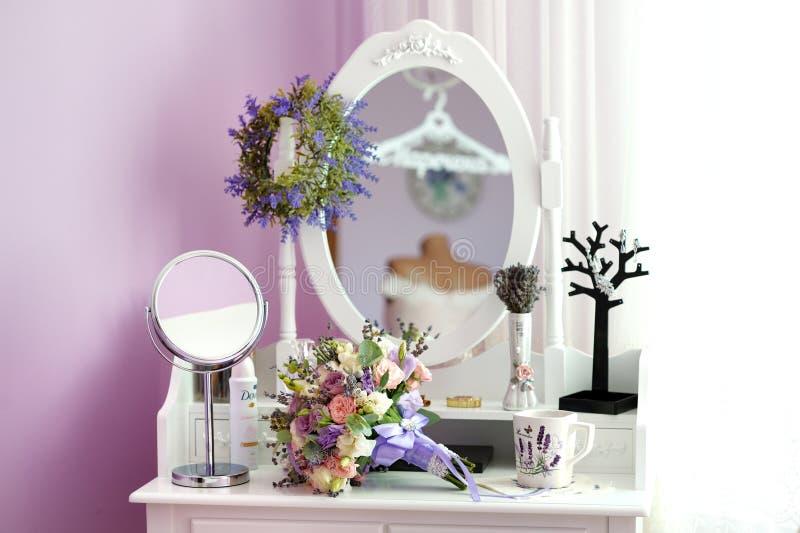 Gifta sig buketten och kopp te på nattduksbordet med spegeln royaltyfri bild