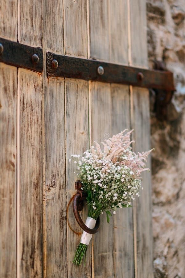 Gifta sig den brud- buketten av gypsophilaen på en gammal trädörr Wedd royaltyfri foto