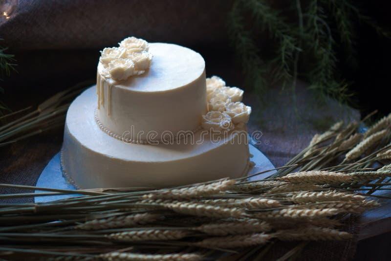 Gifta sig den kräm- kakan på lantlig bakgrund Härligt gourmet- syrligt som dekoreras med vita rosor och öron av vete royaltyfria foton