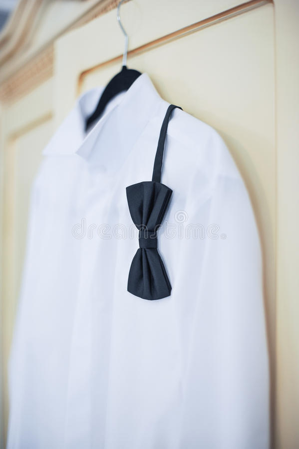 Gifta sig den ljusa vita skjortan och den svarta pilbågen Formell brudgumskjorta med den svarta flugan Elegant vit brudgums skjor arkivfoton