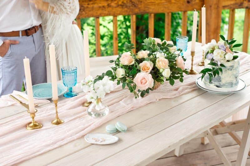 Gifta sig garneringtabellen i trädgården, blom- ordning, stearinljus i stiltappningen på utomhus- caken blommar br?llop arkivfoton