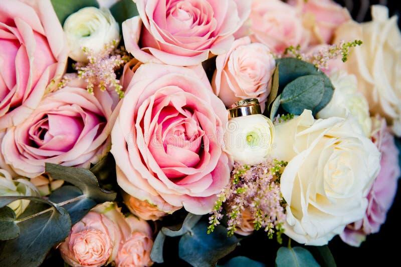Gifta sig guld- cirklar på en bukett av blommor arkivfoto