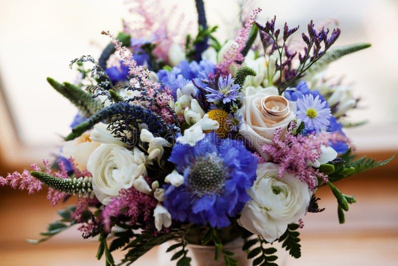 Gifta sig guld- cirklar på en bukett av blommor fotografering för bildbyråer