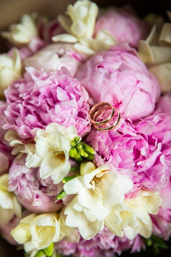 Gifta sig guld- cirklar på en bukett av blommor arkivbild