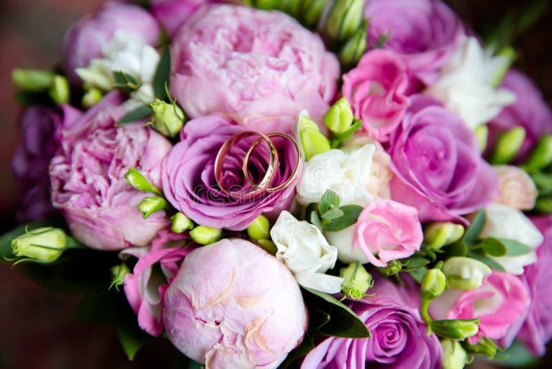 Gifta sig guld- cirklar på en bukett av blommor royaltyfri foto