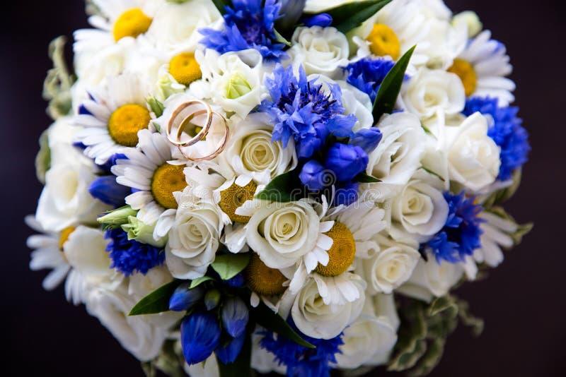 Gifta sig guld- cirklar på en bukett av blommor royaltyfri fotografi