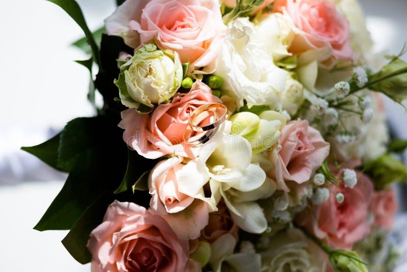 Gifta sig guld- cirklar på en bukett av blommor royaltyfria foton