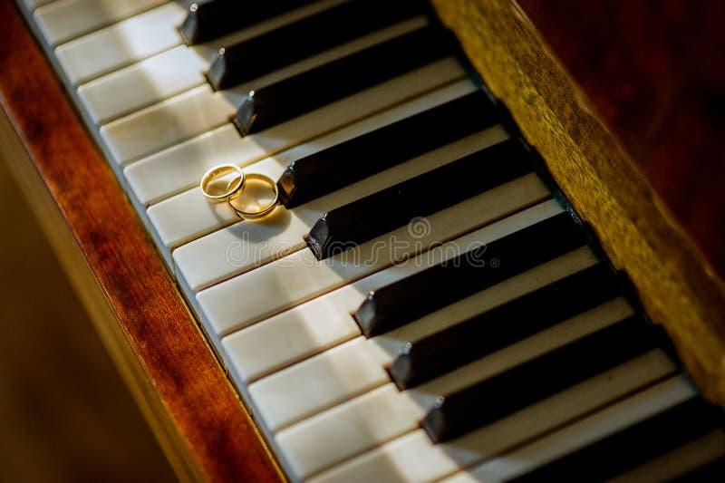 Gifta sig guld- cirklar på pianot closeup man för begreppskyssförälskelse till kvinnan Brud- och brudgumtillbehör royaltyfria foton
