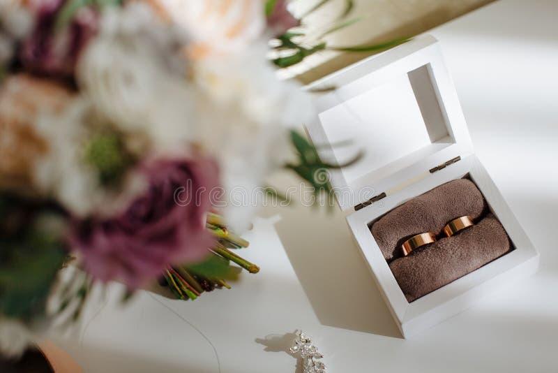 Gifta sig guld- sned boll ringer i träask och bukett med härliga rosor förberedelse royaltyfria bilder
