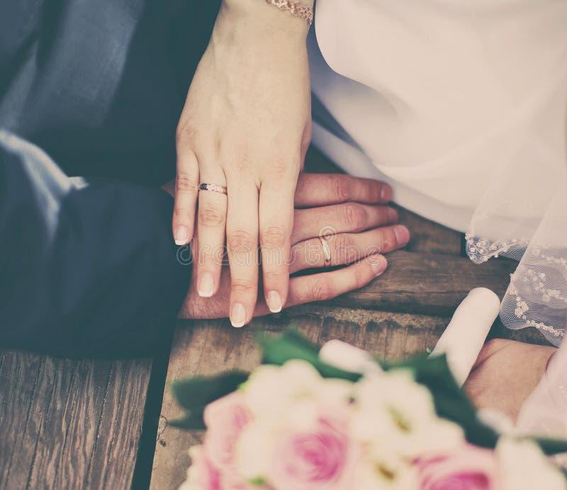 Gifta sig händer för parbrud- och brudguminnehav med cirklar, bukett av blommor royaltyfria foton