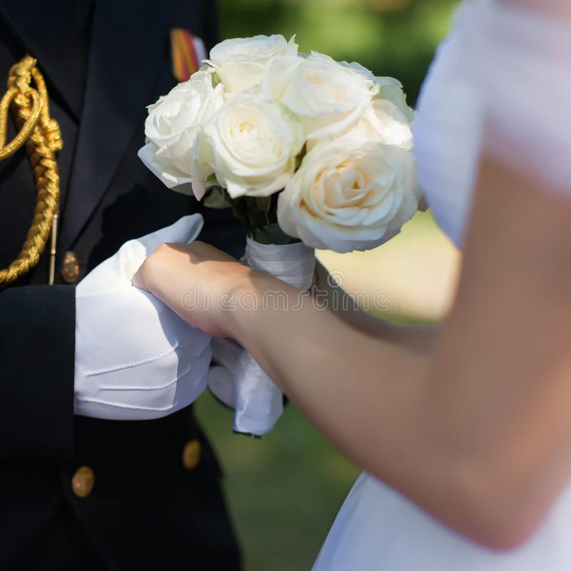 Gifta sig händer med bröllopbuketten från vita rosor utomhus royaltyfri foto