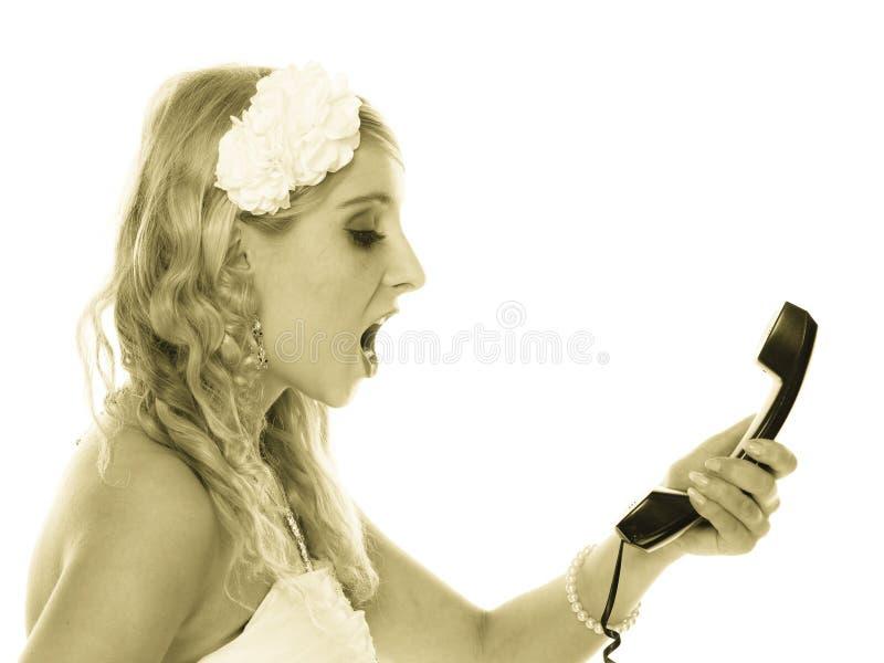 Gifta sig. Ilsken kvinnaraseribrud som talar på telefonen arkivfoto
