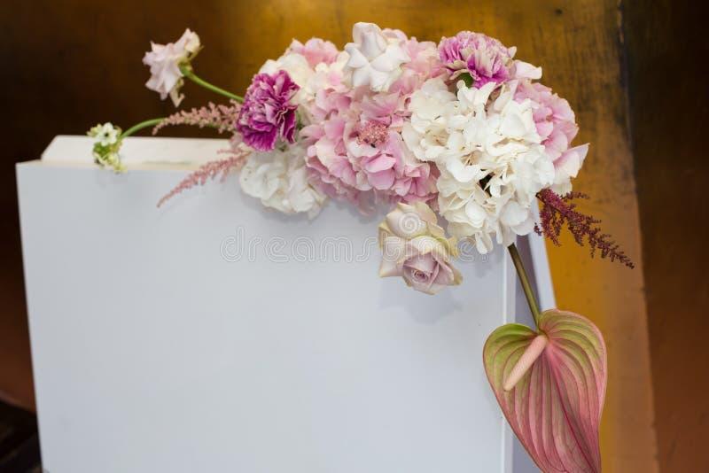 Gifta sig inbjudanplattan dekorerade med den nya astilbe-, nejlika-, riddarsporre-, ornithogalum-, authurium- och vanlig hortensi arkivfoto