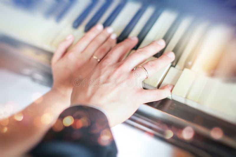 Gifta sig nyligen händer för par` s med vigselringar nygifta personer som visar deras vigselringar på piano arkivbild