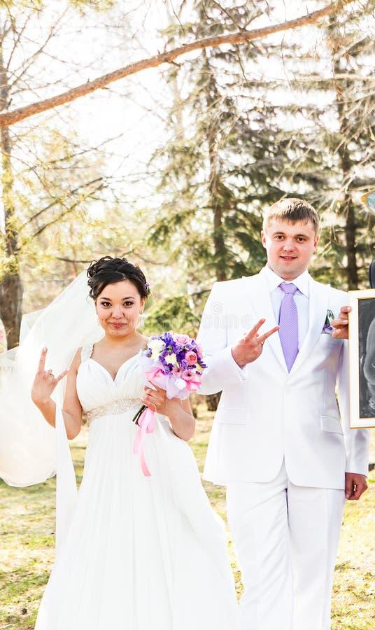 Gifta sig nyligen par som går galna Brudgum och brud royaltyfri foto
