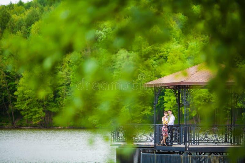 Gifta sig nyligen par som omfamnar bredvid en sjö arkivfoto