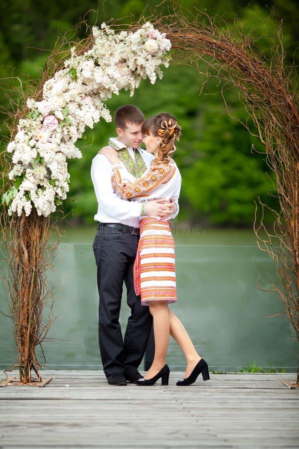 Gifta sig nyligen par som omfamnar bredvid en sjö arkivbilder