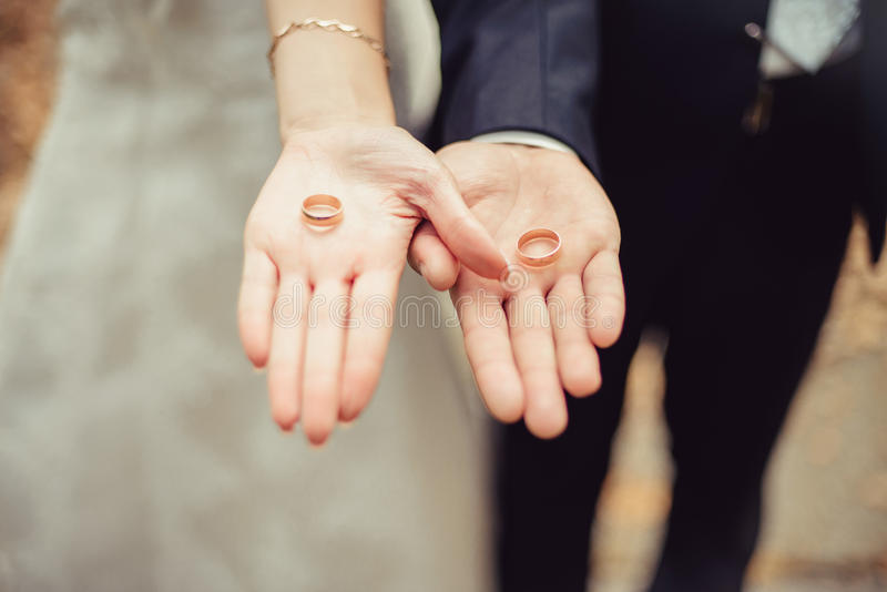 Gifta sig nyligen parets händer med vigselringar royaltyfri foto