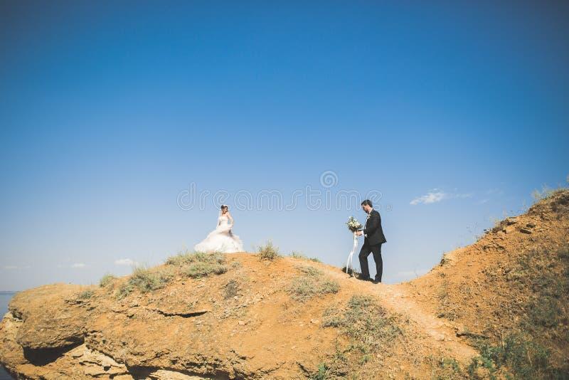 Gifta sig par, brudgummen, bruden med buketten som poserar nära havet och blå himmel arkivbild