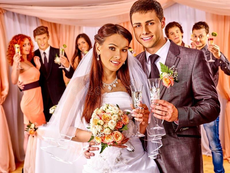 Gifta sig par och gäster som dricker champagne royaltyfria bilder