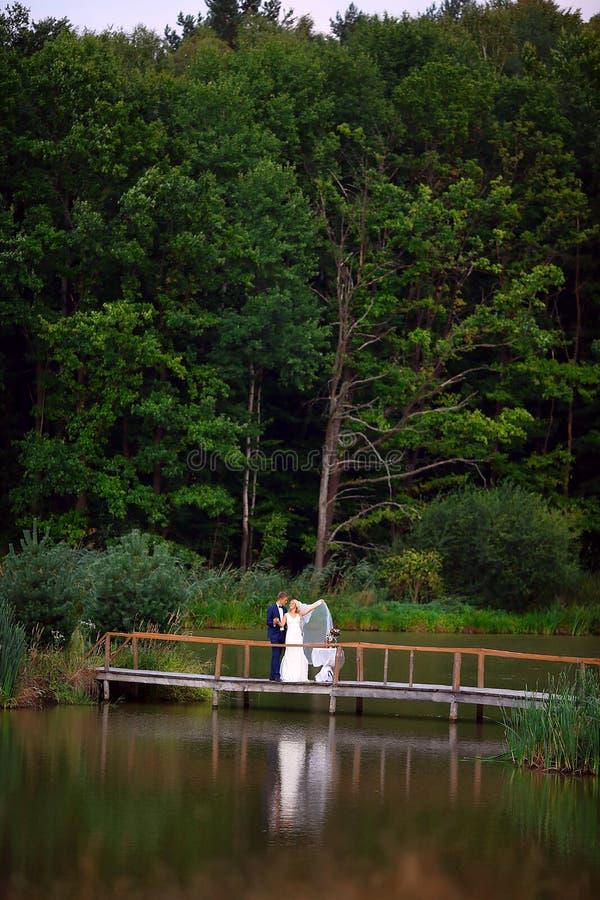 Gifta sig par som är förälskade på bröllopdag rymmer brudgummen, bruden i hennes armar nära den härliga sjön i selektiv fokus för royaltyfri bild