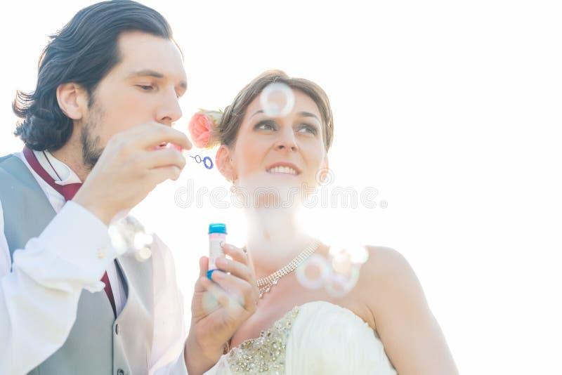 Gifta sig par som blåser såpbubblor arkivfoton