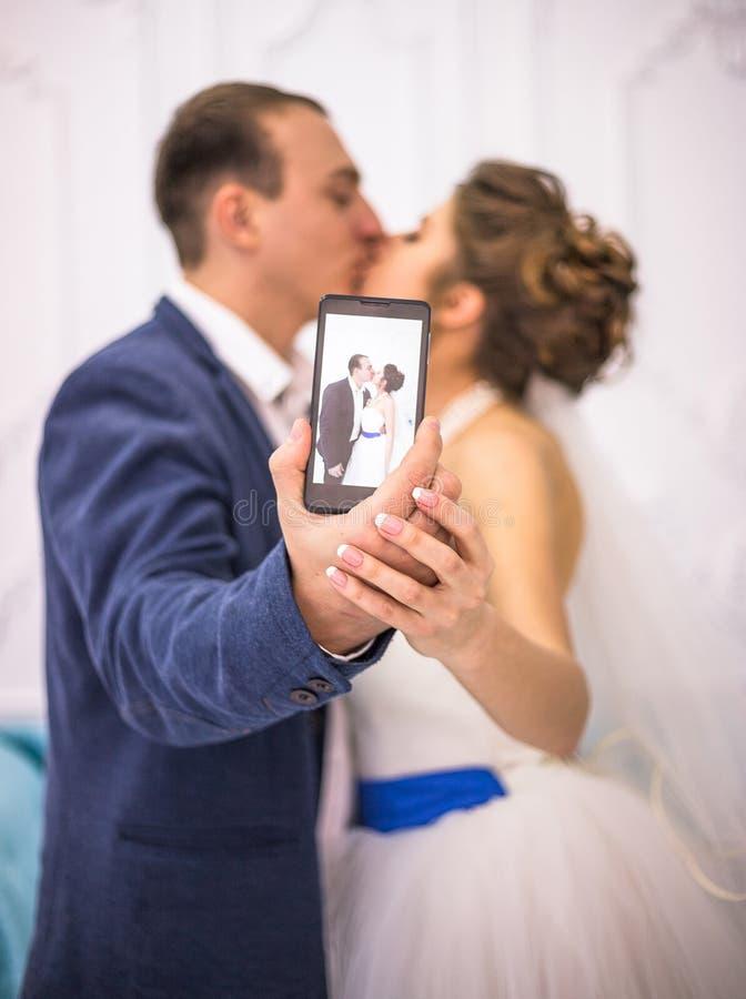 Gifta sig par som in gör selfie på Smart-telefonen arkivfoton