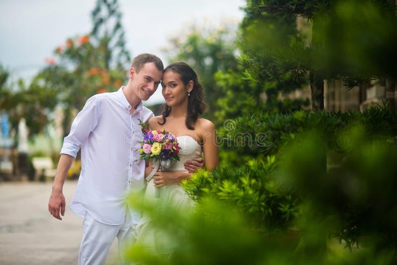 Gifta sig par, står en härlig ung brud och brudgum, i parkera utomhus och att omfamna och och att le royaltyfria foton