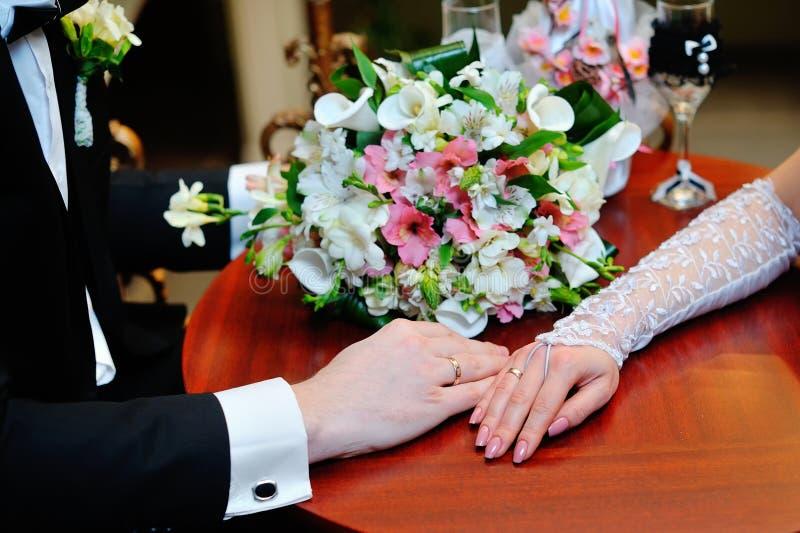 Gifta sig parinnehavhänder på bukett Brudgum och brud i PA royaltyfri fotografi