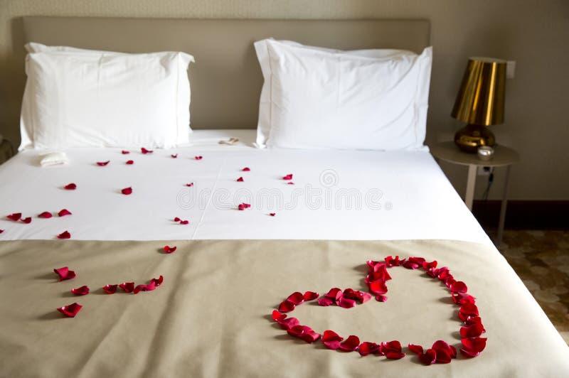 Gifta sig säng som överträffas med rosa kronblad arkivbild