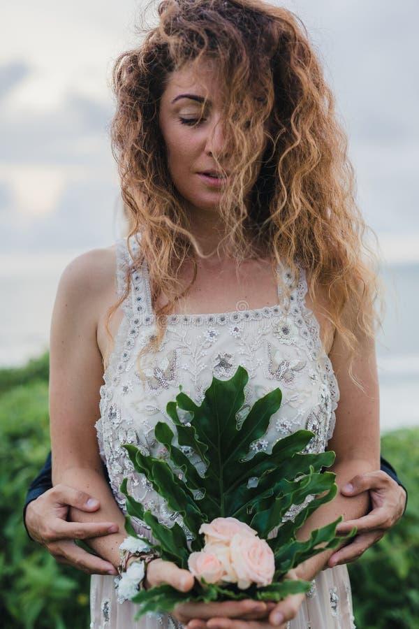 Gifta sig som är lovestory, precis gift par nära havet på solnedgången royaltyfri bild