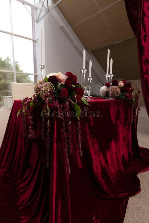 Gifta sig tabellen för bruden och brudgummen som dekoreras med burgundy tyg och buketter runt om kanterna royaltyfri foto