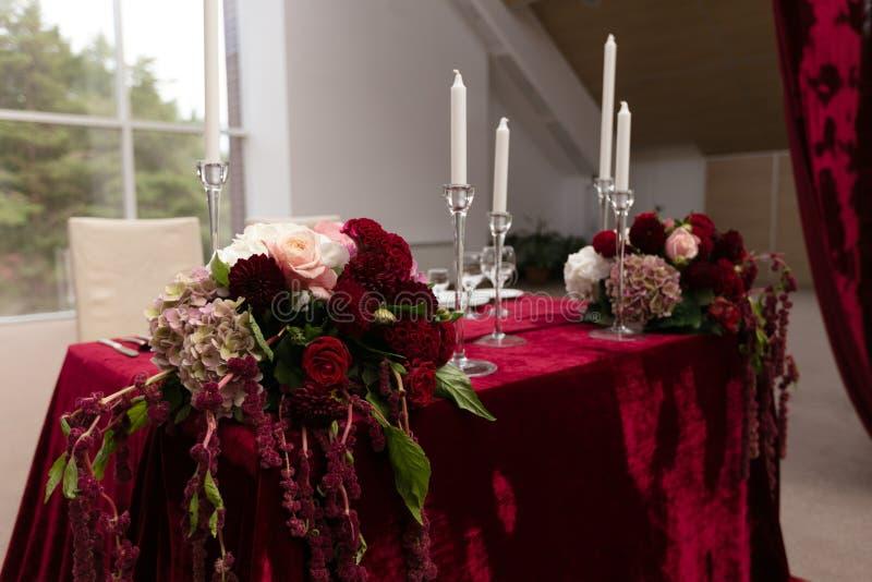 Gifta sig tabellen för bruden och brudgummen som dekoreras med burgundy tyg och buketter runt om kanterna royaltyfri bild