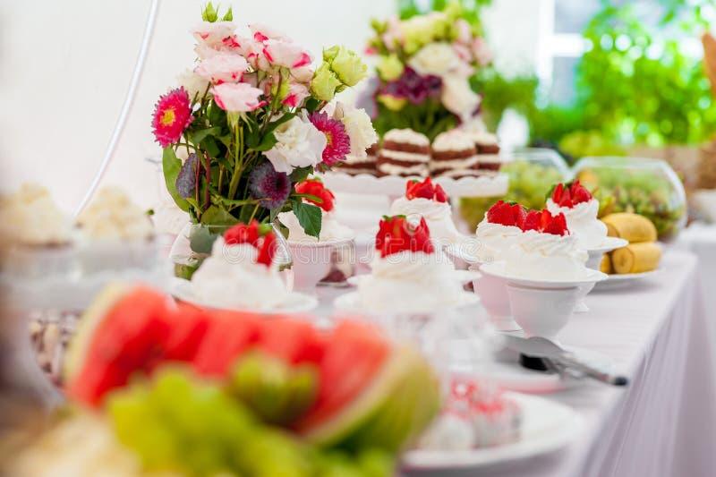Gifta sig tabellen med den söta vita kakan och jordgubben överst Blommor i bakgrund royaltyfri foto