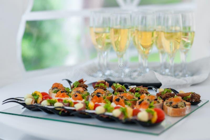 Gifta sig tabellen med mat Aptitretare på tabellen Fisk och rått kött med grönsaker Champagne Glass i bakgrund royaltyfri bild