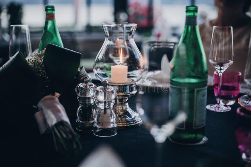 Gifta sig tabellen med stearinljus, bestick och plattor, champagnedrink och exponeringsglas på mottagandet utomhus i aftonen lyxi royaltyfria foton