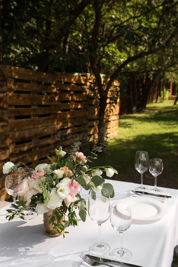 Gifta sig tabellinst?llningen dekorerade med nya blommor i en m?ssingsvas Gifta sig som ?r floristry Banketttabell f?r g?ster uto royaltyfria foton